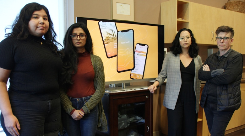Image of Pollution Reporter project team standing in front of screen showing images of the app on mobile phones.